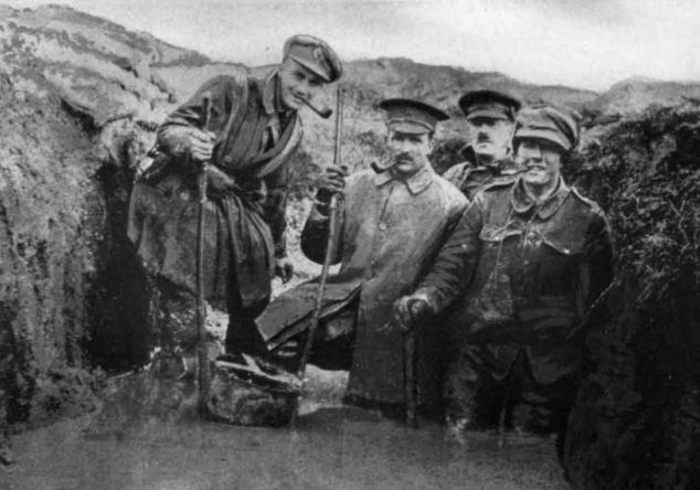 Deluged: Three members of Harry's company can be seen here posing in a trench flooded with mud almost to waist height