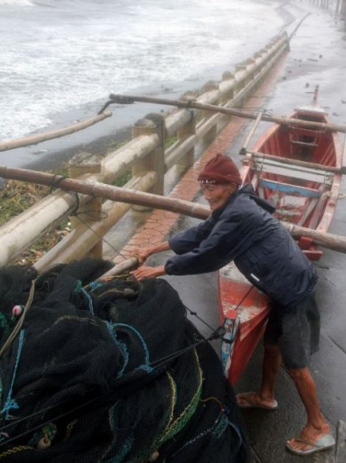 A fisherman secures his wooden fishing boat along the sea wall amidst strong winds as Typhoon Haiyan hit the city of Legaspi, Albay province, south of Manila
