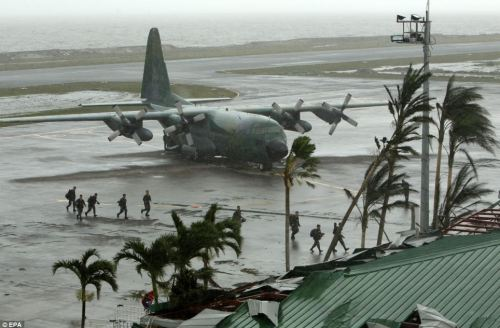 Washed up: Filipino soldiers disembark from a plane stopped at the devastated airport in Tacloban city, Leyte