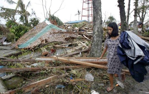 Collapsed: A resident walks past her destroyed home - flattened by piles of wood and branches from nearby trees - in Tacloban city