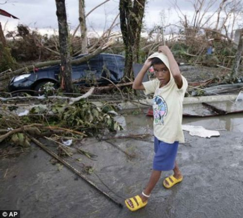 A boy walks past the devastation brought about by powerful typhoon Haiyan at Tacloban city