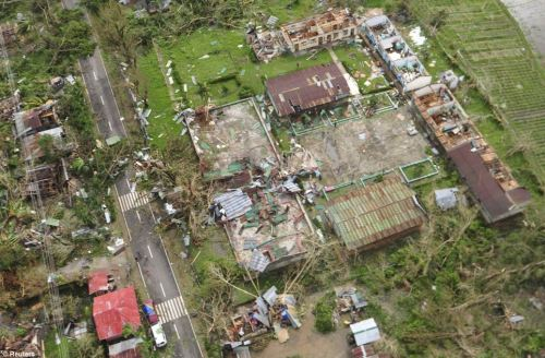 From above: An aerial view shows badly damaged houses, including many without a roof, and blocked roads in Iloilo Province