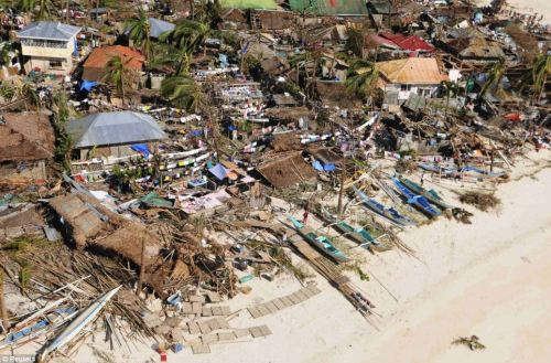 Badly hit: A group of houses in a coastal community in Iloilo Province, central Philippines, that have been destroyed. Boats lie thrown along the coastline also