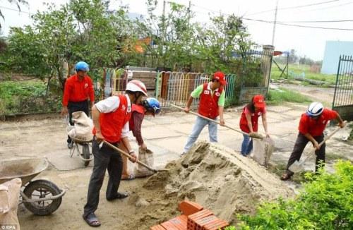 Braced: Red Cross staff in Da Nang, Vietnam, fill sandbags in preparation for the coming storm