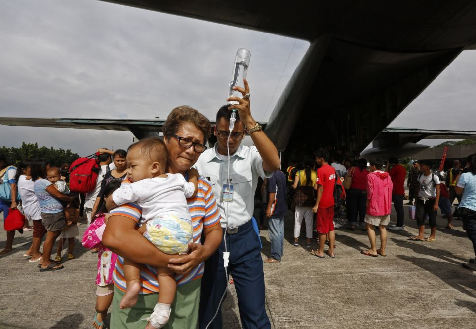 Evacuation: An ill baby, hooked up to a drip, disembarks from a Philippine Air Force C-130 cargo plane at Villamor Airbase