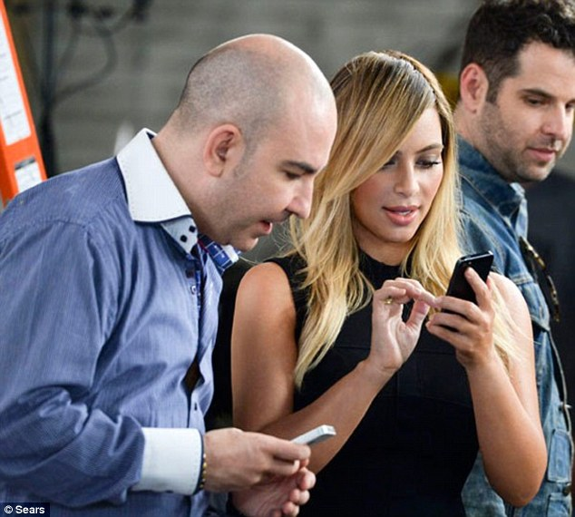 What does yours say?: Kim checked out her smart phone during the shoot