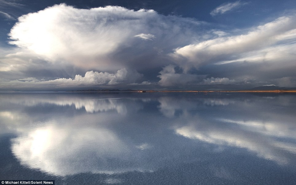 This dreamlike image appears to show an island, but the stillness of the atmosphere creates a a beautiful reflection of the cloudy sky