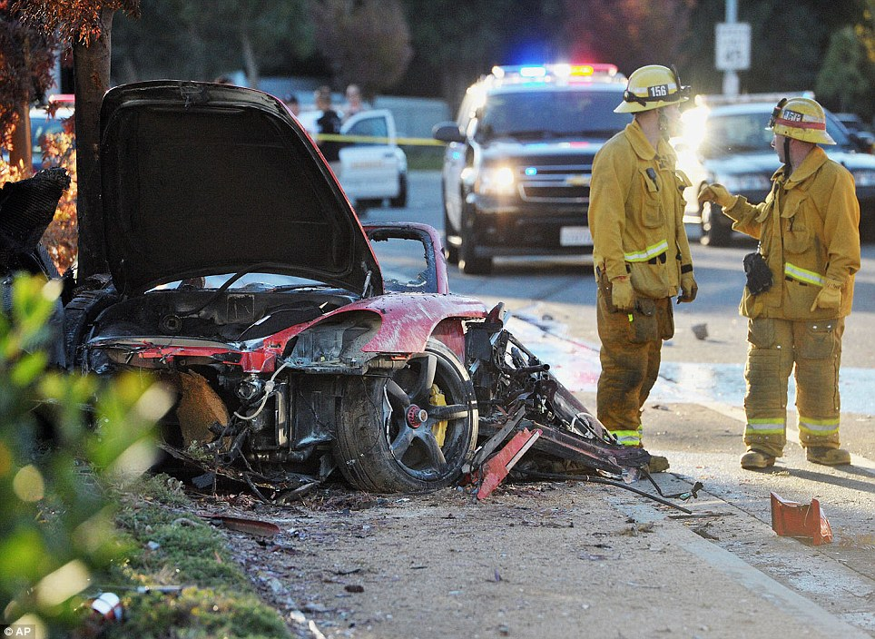 Horror crash: First responders gather evidence near the wreckage of a Porsche sports car that crashed into a light pole on Hercules Street near Kelly Johnson Parkway in Valencia on Saturday, November 30, killing actor Paul Walker