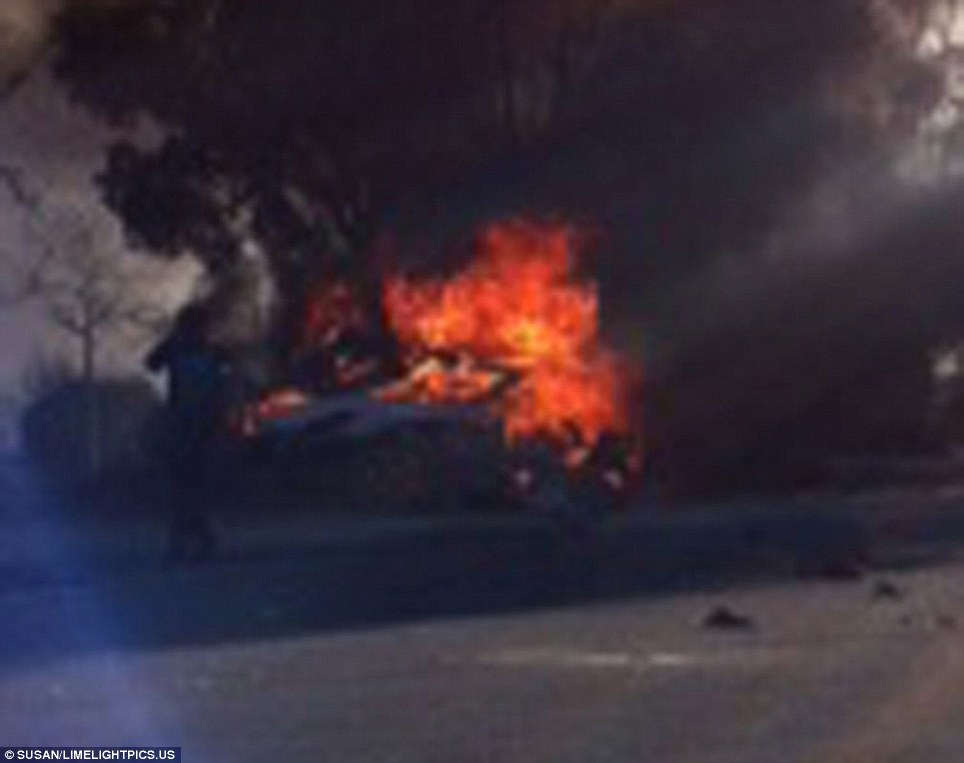 Engulfed: This witness photo shows the Porsche completely engulfed by flames after the driver lost control, hitting a pole and killing himself and Paul Walker