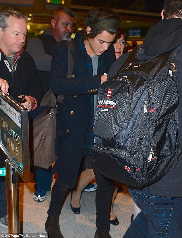 We're back: Harry Styles, 19, seemed keen to get through the airport but was later spotted looking cheerier as he headed out for dinner in Soho, stopping to chat to fans