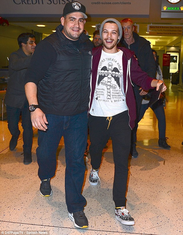 No jet lag here: Louis Tomlinson, 21, was in high spirits despite the late hour as he cuddled up to one of the band's bodyguards as they made their way through JFK