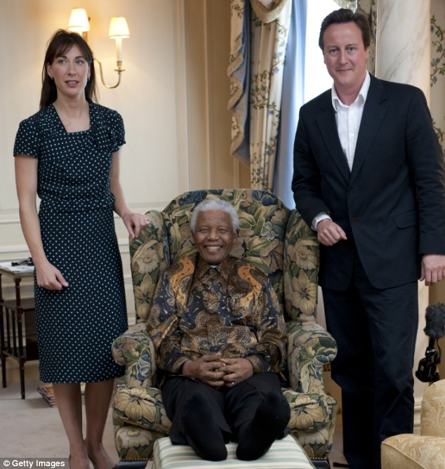 Representing Britain: Prime Minister David Cameron and his wife Samantha, seen with Mandela at a photoshoot for his 90th birthday in London, will pay their respects