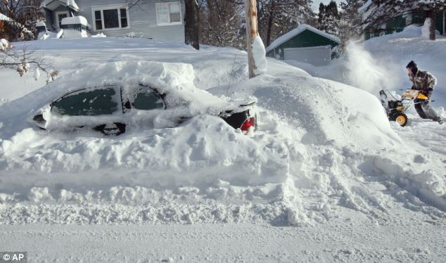 Winter: Scott Asperheim of Duluth, Minnesota clears the sidewalk around his home from several feet of snow