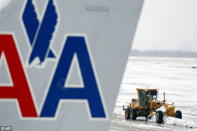 Grounded: Snow removal equipment clears the wet sleet on the ramp area at Dallas-Fort Worth International Airport on Friday. More than 1,000 flights have been canceled from the airport