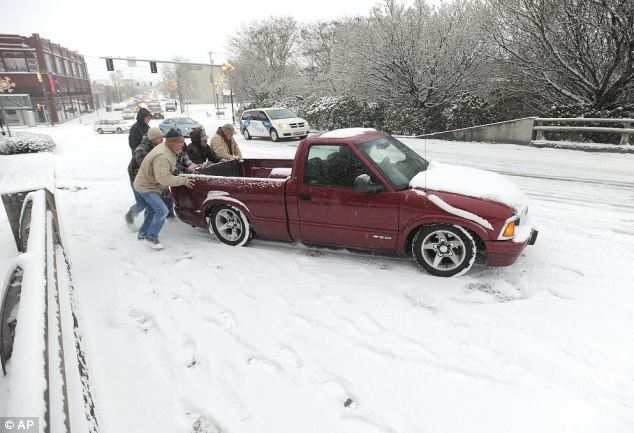 Oops: Passersby help a pickup get up the incline on the Lyon Street Bridge Friday morning in Albany, Oregon