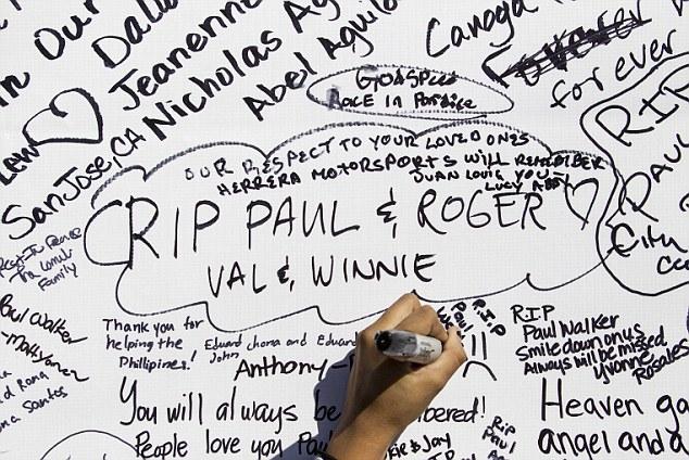 Los aficionados se agolpan el sitio durante un mitin y el coche memorial de cruceros en Valencia, California, Domingo, 08 de diciembre 2013 para recordar el actor Paul Walker y su amigo Roger Rodas, quien murió en un accidente de coche de fuego el pasado sábado