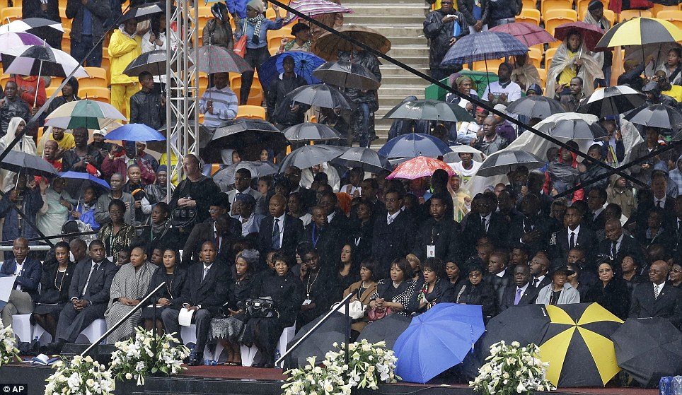 Sombre occasion: Members of Nelson Mandela's family take their seats amid heavy rain ahead of his memorial service at the FNB Stadium in Soweto, near Johannesburg