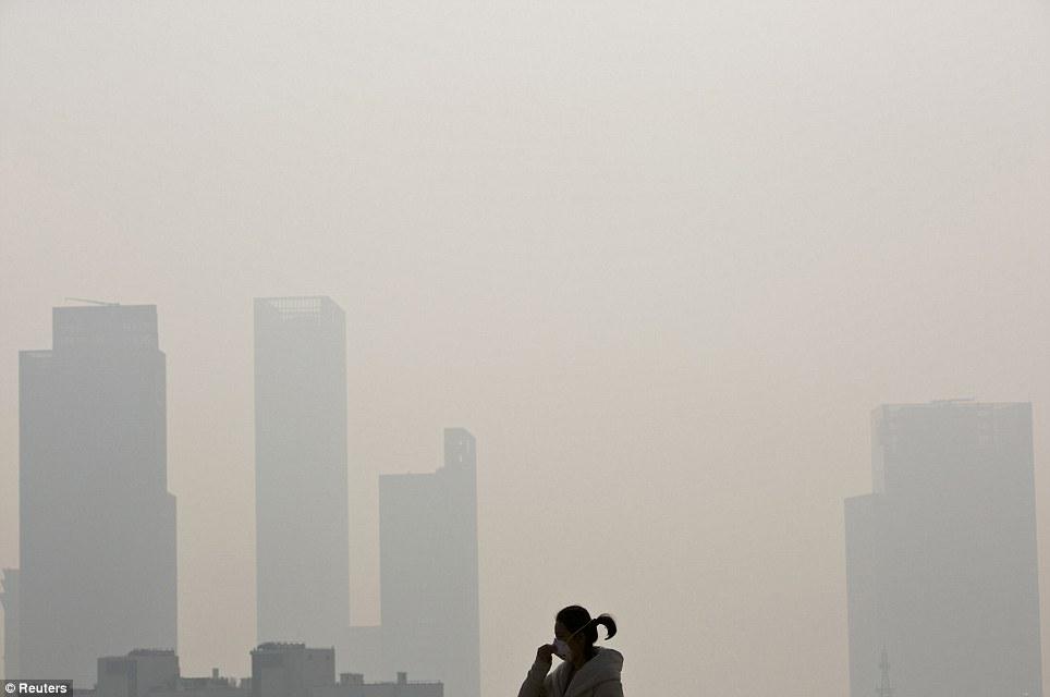 Pollution: Une femme portant un masque sur un pont dans le centre de Shanghai le 5 Décembre, lorsque le dernier purée de pois a commencé.  Les autorités sont à introduire de nouveaux bus à faibles émissions de carbone