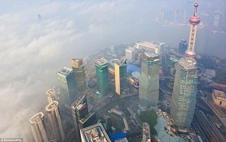 Dangereux: A Shanghai, l'horizon emblématique dont le 1535 m Oriental Pearl Tower (à droite) est apparu naufragé par un tourbillon d'épaisseur du smog, qui a laissé les citoyens à risque de cancer