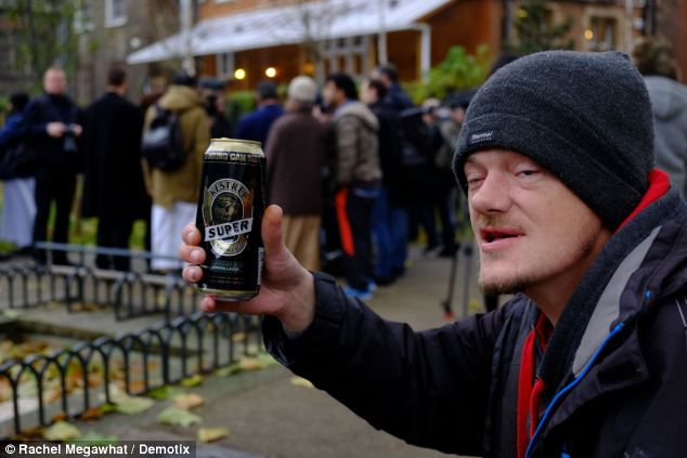 A local man enjoys his drink as Choudary and others protest against the sale of alcohol in the UK