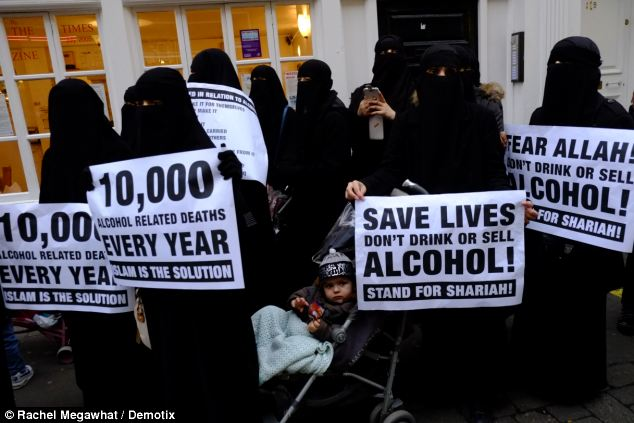 Protestors in burkhas hold up posters encouraging the ban of alcohol, in the name of Sharia Law