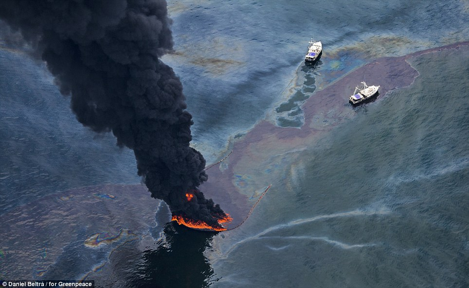 Two ships monitor a controlled burn from oil that was spilled from the wellhead. To aid in clean-up efforts, 5,300 vessels of opportunity were hired from around the area