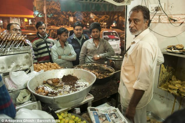 Publicity stunt: Prem Singh pulls a crowd outside his restaurant in Deli with his ability to retrieve frying fish from hot oil with his bare hands