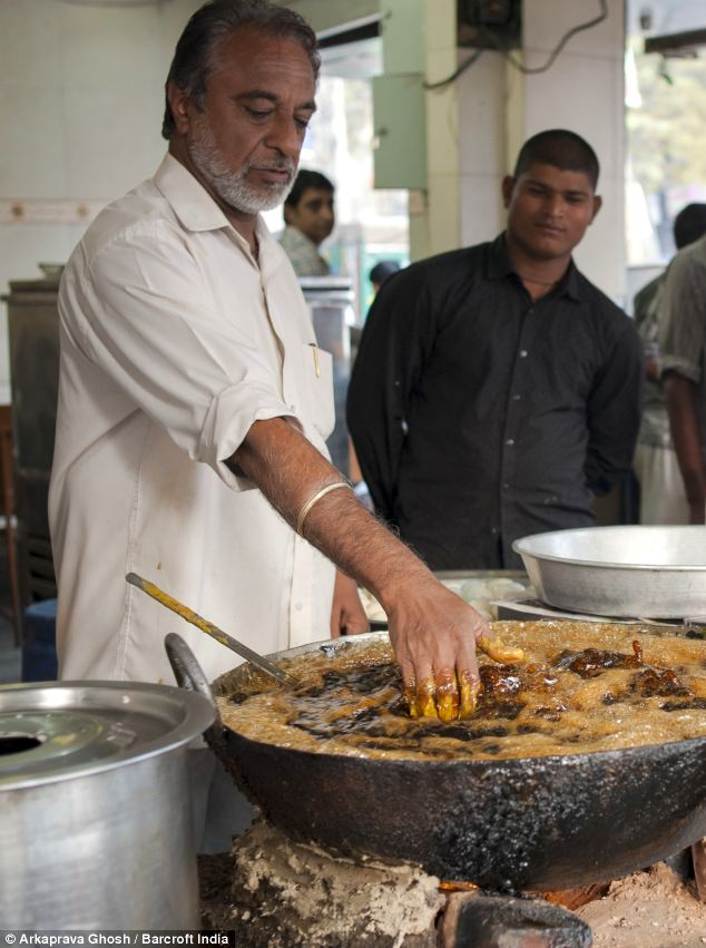 Scorching: The oil into which Prem Singh dips his fingers is heated over a fire to about 200C - enough to deep fry skin