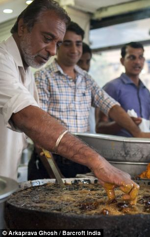 Prem Singh picks up a piece of fried fish with his bare hand from the hot oil
