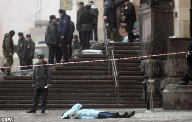 Body: A victim lies in front of the station entrance as officials survey the damage