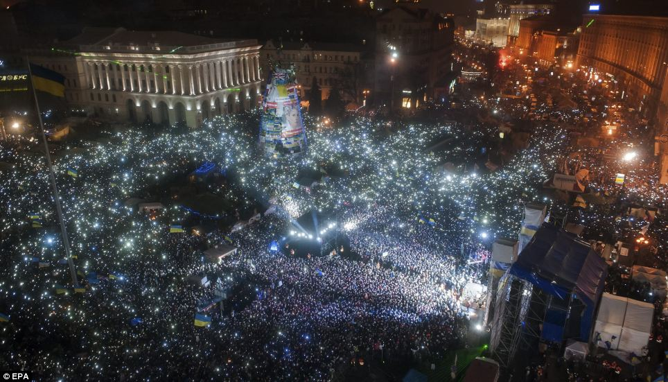 Ukrainians light screens and mobile phones as they sing the National anthem during the 2014 New Year celebrations at the pro-European supporters' tent camp at Independence Square in Kiev, Ukraine
