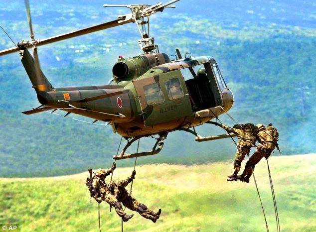 Japan Ground Self Defense Force soldiers rapel down from a transport helicoptor UH-1