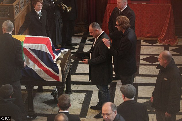 Funeral: Ronnie Biggs son Michael holds his father's cap as he is comforted by Great Train Robbery ringleader Bruce Reynolds' son Nick