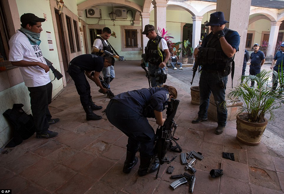 Police officers are forced to surrender their weapons to armed vigilantes in Paracuaro yesterday after the group seized control