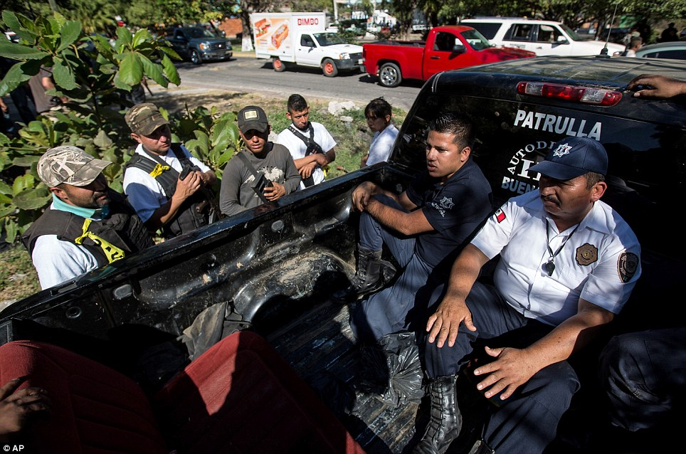 Detained: Local vigilantes arrested police in Paracuaro in south-west Mexico yesterday as they seized back control of the town from the Knights Templar drugs gang
