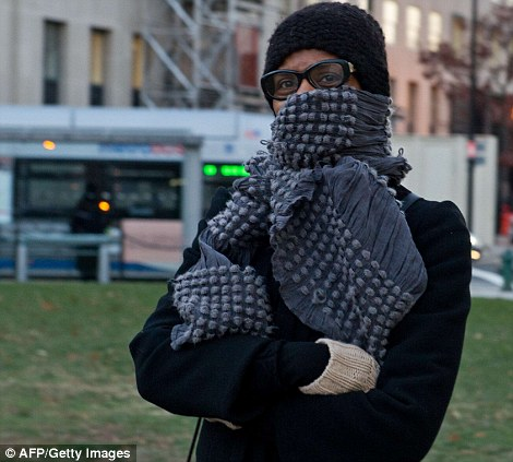 A woman bundled against the cold walks from the metro as temperatures with the wind chill making it feel even colder in DC