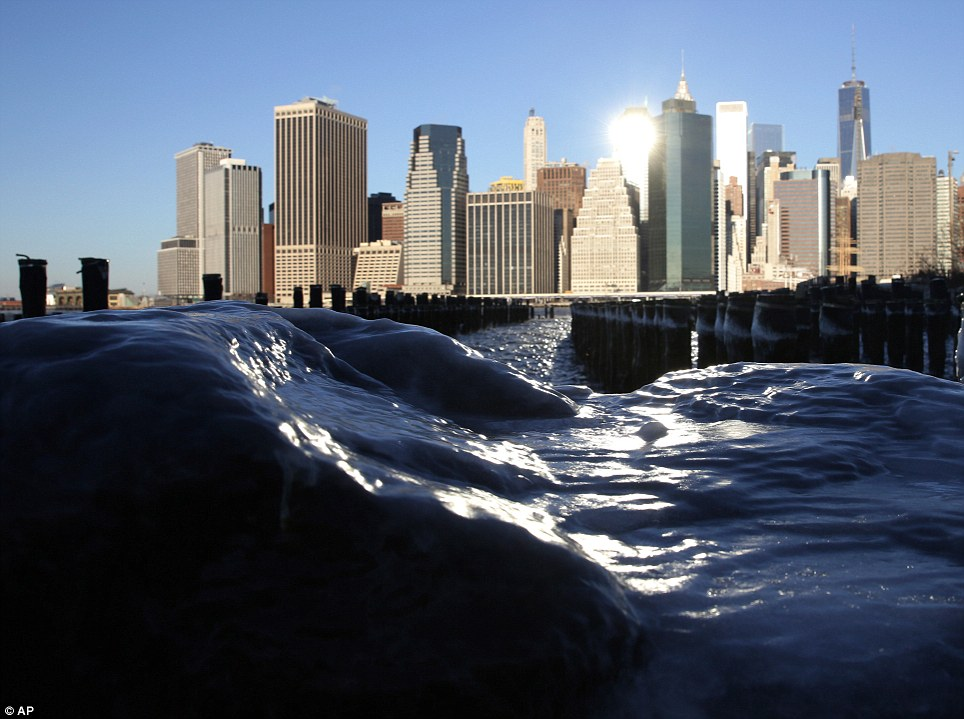 Ice forms on rocks on the Brooklyn waterfront across from lower Manhattan in New York on Tuesday