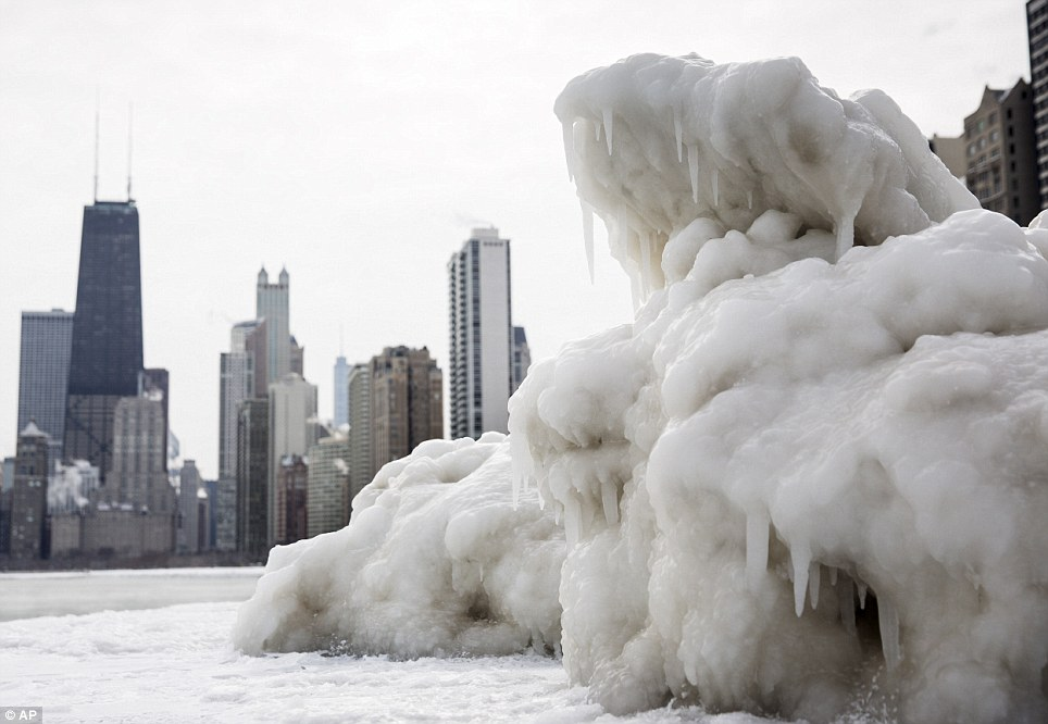 The Chicago skyline is seen behind a large chunk of ice near North Avenue Beach as cold temperatures remain with wind chills nearing minus 30F on Tuesday