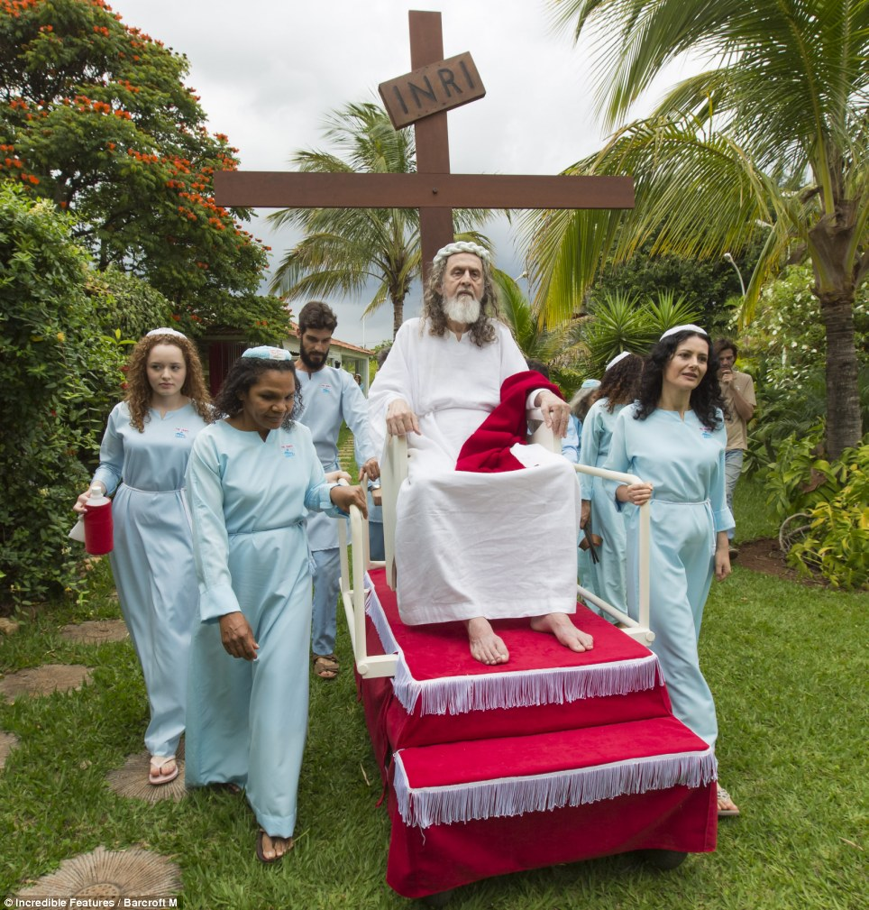 Preacher and leader: Inri Christo's loyal followers push his pulpit out into the garden in order to listen to his words as 'Jesus'