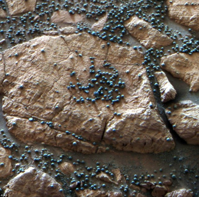 These hematite-rich spherules were embedded in this Martian rock like blueberries in a muffin and released over time by erosion. The Mars Rover Opportunity found this cluster at its Eagle Crater landing site and analysed their composition with its spectrometers. Hypotheses about their formation have contributed to the story of water on Mars