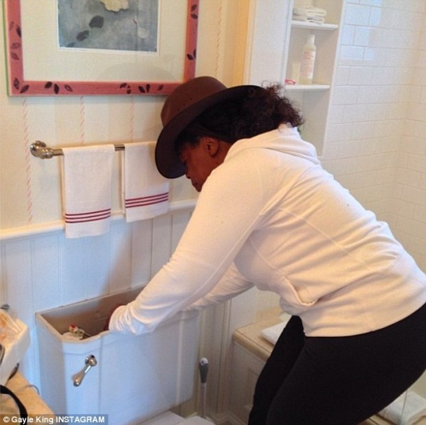 Tinkering with her throne: Oprah Winfrey, 59, was snapped by best friend Gayle King while fixing her toilet at her Maui home on Sunday