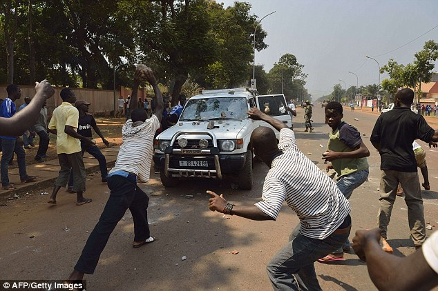 Violence: People throw stones at a car transporting two children of an ex-Seleka colonel at the 'UN crossroad' on Sunday in Bangui