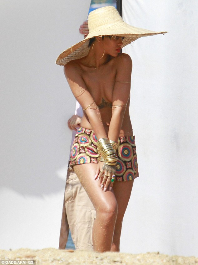 Practised pout: The singer smouldered from beneath her large floppy straw hat