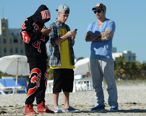 Text for success: Justin spent much of his time checking his phone with his friend on the beach