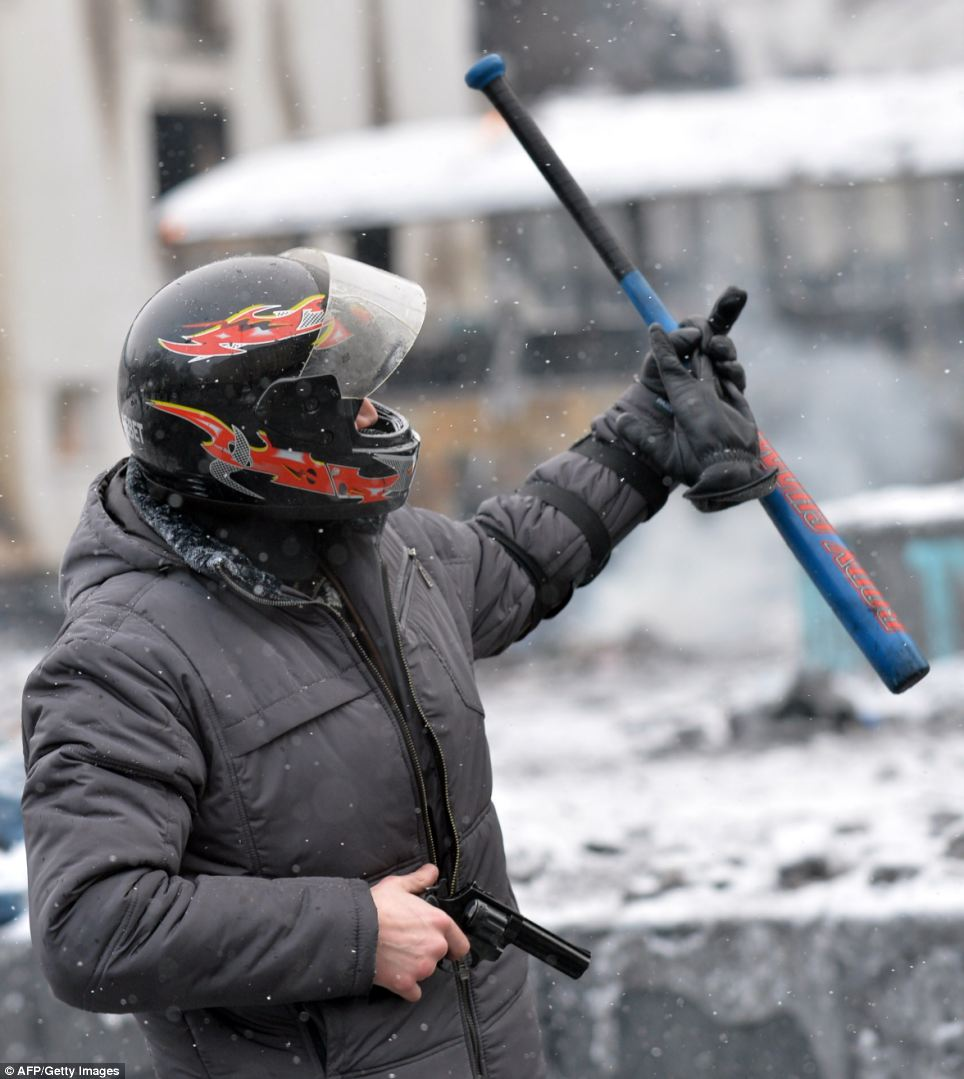 A demonstrator holds a hand gun as protesters clash with police in the center of Kiev