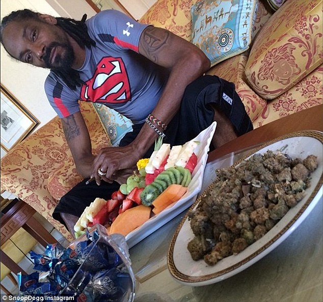 Bad boy: Snoop Lion, aka Snoop Dogg, poses with large bowl of what appears to be uncut cannabis in his hotel suite on the Gold Coast on Tuesday