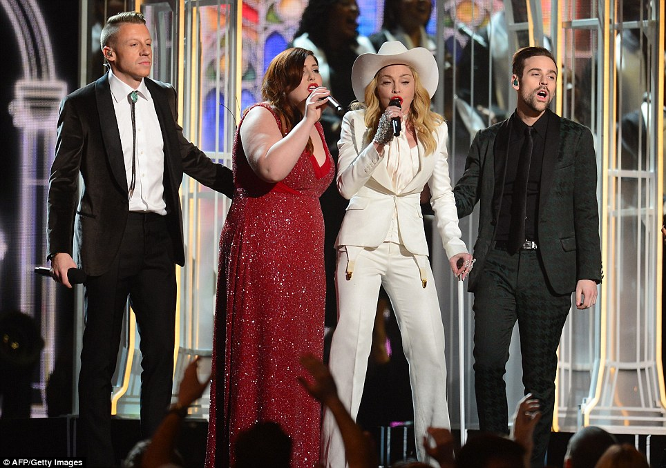Macklemore (L), Ryan Lewis (2nd R), Mary Lambert (2nd L), Madonna (C) embrace on stage after performing the song 'Same Love' while Queen Latifah officiated over a mass wedding at the Grammy Awards