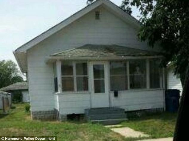 Eerie: Cops and child protection workers were also spooked during visits to the home in Gary, Indiana (pictured). In this image, a figure appears in a window, right, although no one was home