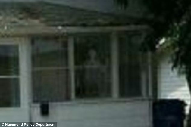 What is it? A close-up of the image shows the cloudy white figure in the window of the home