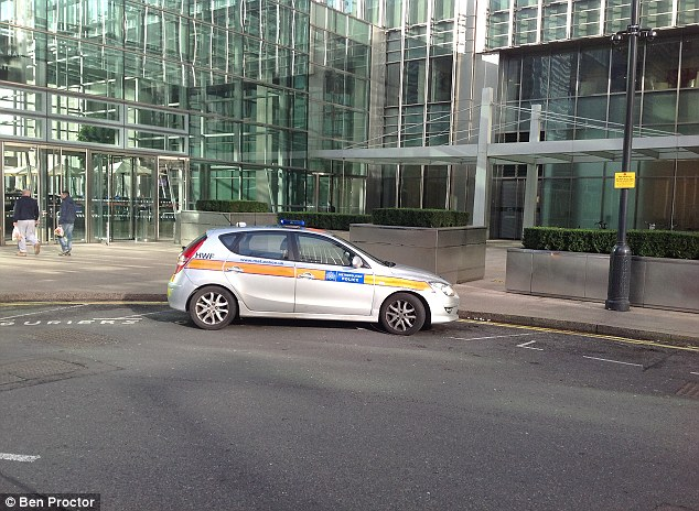 Investigation: Police at the scene outside the JP Morgan building this morning, where the man was found dead at around 8am